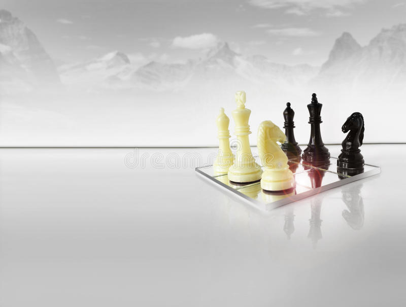 Strategy. Chess pieces on white reflective foreground with abstract winter mountain scape in background royalty free stock images