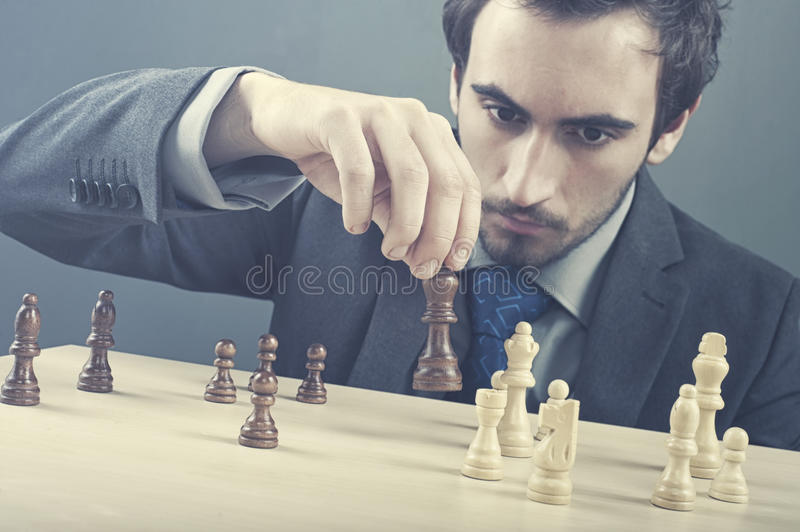 Strategy. Business man prepares his strategy with chess pieces royalty free stock image