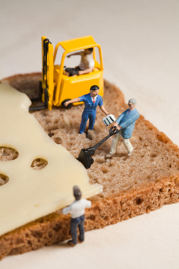 Strategy And Planning. A tiny model figure of a foreman directs his miniature team in the making of a cheese sandwich using a forklift and loading equipment stock image