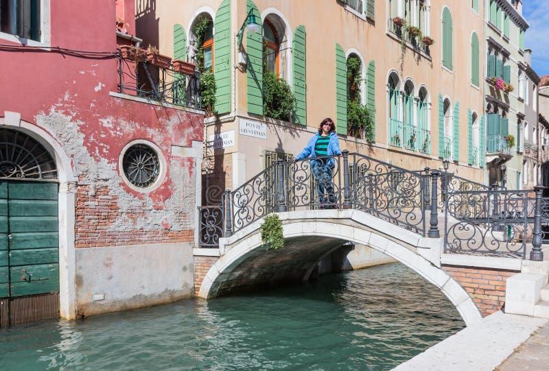 Straten van de stad van Venetië De vrouw in matroos bevindt zich op een brug van Ponte Giustinian over een kanaal in Venetië, Ita stock afbeelding
