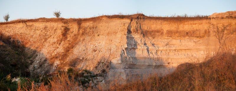Strati del taglio della sabbia nella carriera della sabbia al tramonto fotografie stock