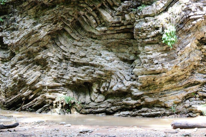 Strati di magma congelato su milioni di anni sulla banca di una torrente montano immagine stock