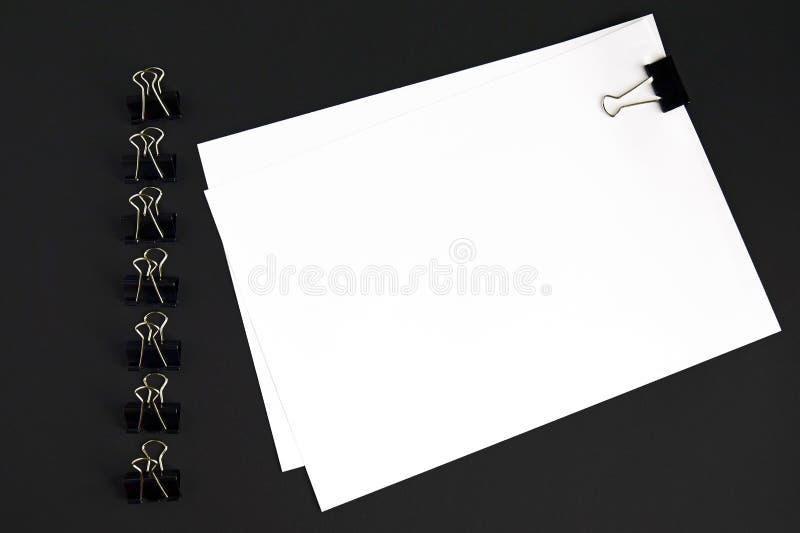 Strati e clip bianchi del raccoglitore su fondo nero, vista superiore, modello fotografia stock
