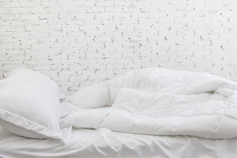 Strati e cuscino bianchi della lettiera nel fondo della stanza bianca Concetto sudicio del letto a tempo la mattina fotografia stock