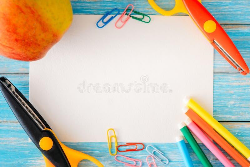 Strato del Libro Bianco vicino a cancelleria e mela su fondo di legno blu, concetto del modello per di nuovo alla scuola immagini stock libere da diritti