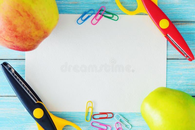 Strato della carta in bianco, due mele e forbici su fondo blu, vista superiore fotografia stock
