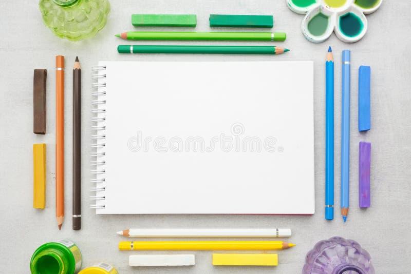 Strato di carta in bianco dello sketchbook, dell'acquerello, dell'acrilico e delle pitture ad olio, matite, pastelli pastelli fotografia stock