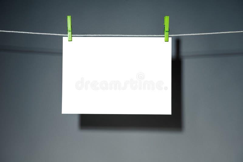 Strato di Libro Bianco per il vostro testo sulla corda con una molletta da bucato verde, sul fondo dell'ombra scura fotografia stock libera da diritti