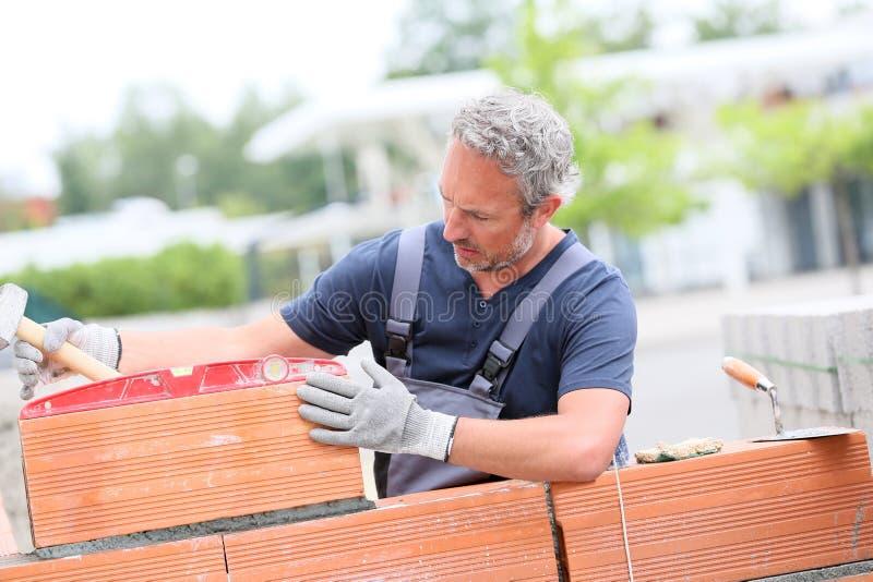 Strato di mattone professionista che fa la costruzione della parete immagini stock