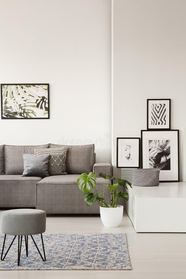 Strato grigio con i cuscini dietro un panchetto su tappeto blu in luminoso immagini stock libere da diritti