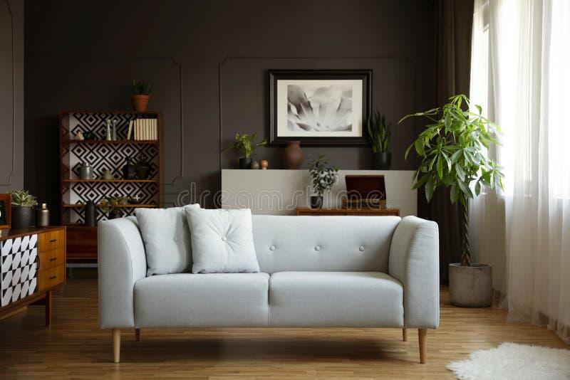 Strato grigio con i cuscini nell'interno d'annata luminoso del salone con le piante ed il manifesto Foto reale fotografia stock libera da diritti