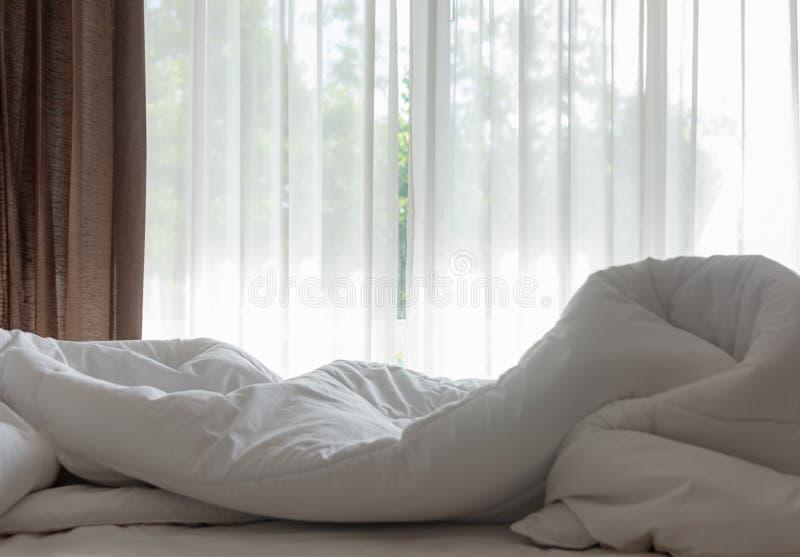 Strato, piumino bianco e cuscino del letto del materasso, incasinati di mattina nella stanza del letto immagine stock