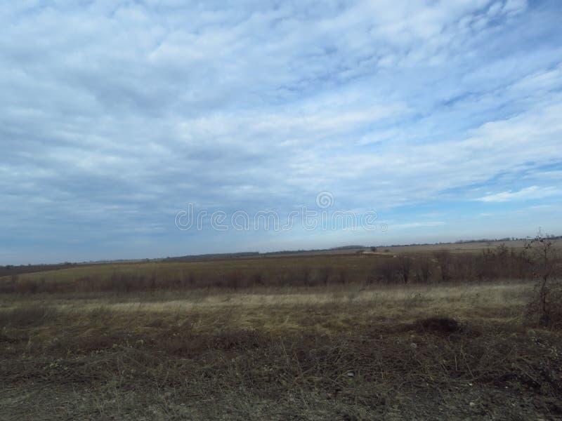 Stratocumulus bas, nuages blanchâtres gonflés et grisâtres Champ nu d'hiver de chute d'automne Campagne Temps sombre images libres de droits