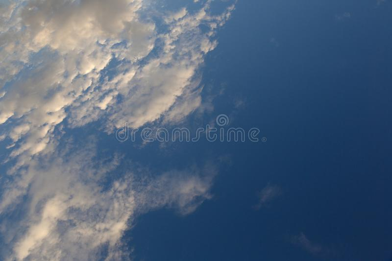 Stratocumulus clouds at the blue sky. A stratocumulus cloud belongs to a genus-type of clouds characterized by large dark, rounded masses, usually in groups stock image