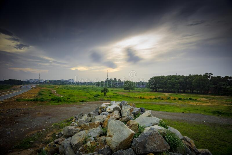 Stratus Clouds Above Green Grass and Beige Stones royalty free stock photos