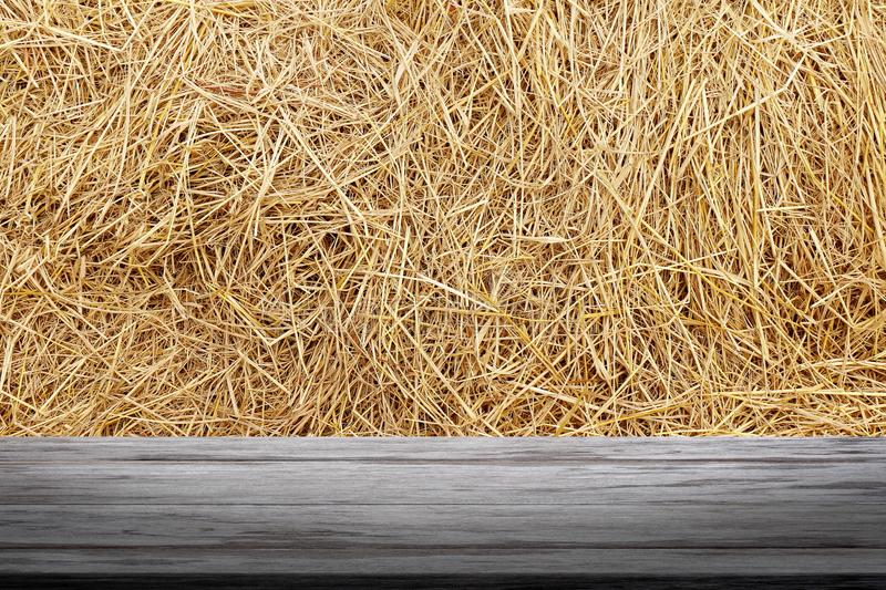 Straw hay backdrop and wood plank, straw wall, straw background texture, wooden floor plank table empty on dry rice straw wall royalty free stock images