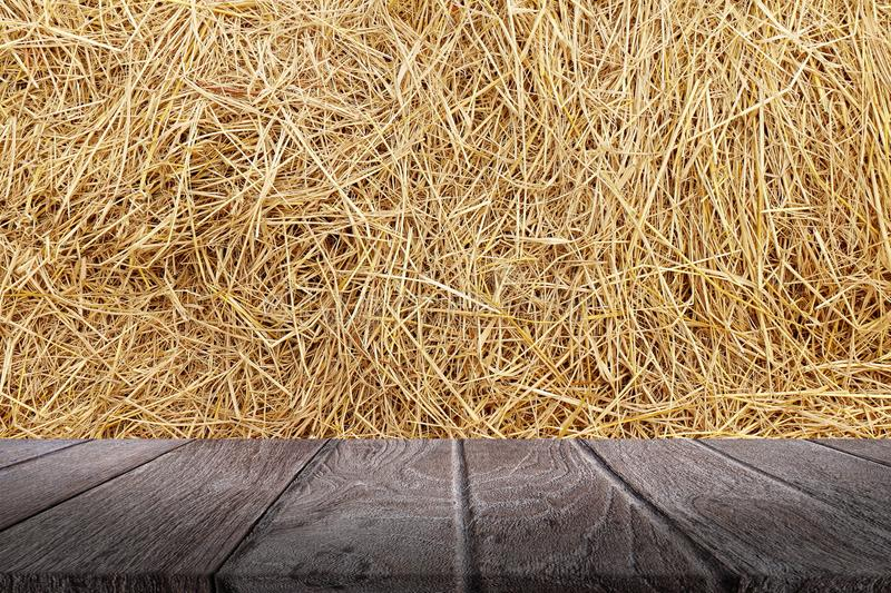 Straw hey background texture, Wooden floor plank table empty on dry rice straw wall background for copy text space, Straw and wood royalty free stock photo