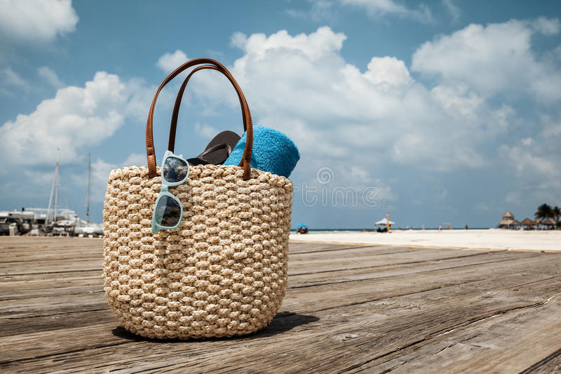 Straw bag on the wooden bridge at tropical beach, Mexico. Straw bag on the wooden bridge at tropical beach, vacation concept stock photo