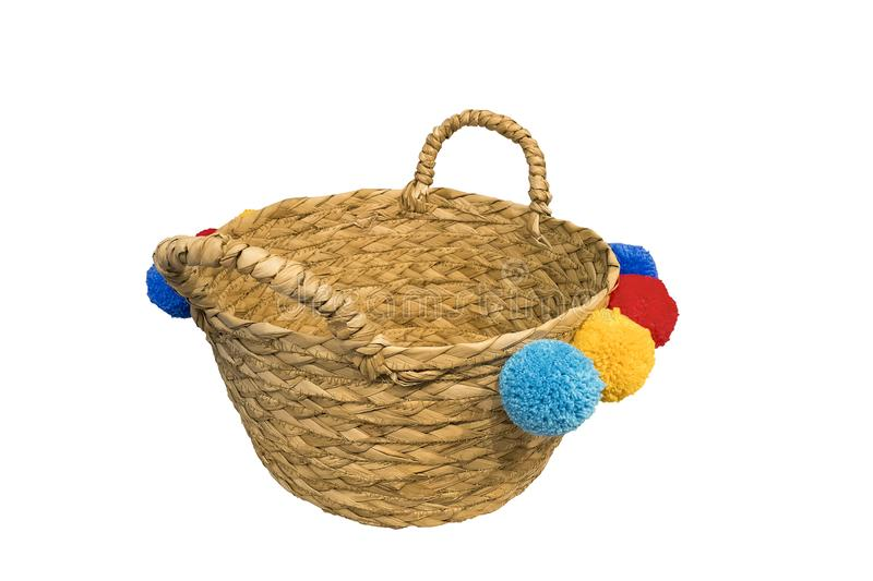 Straw basket with pom poms stock photography