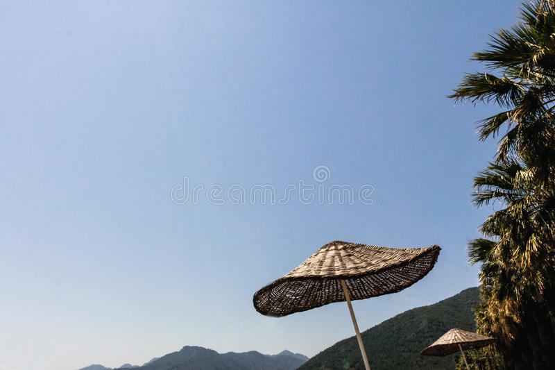 Straw beach umbrella against the sky royalty free stock image