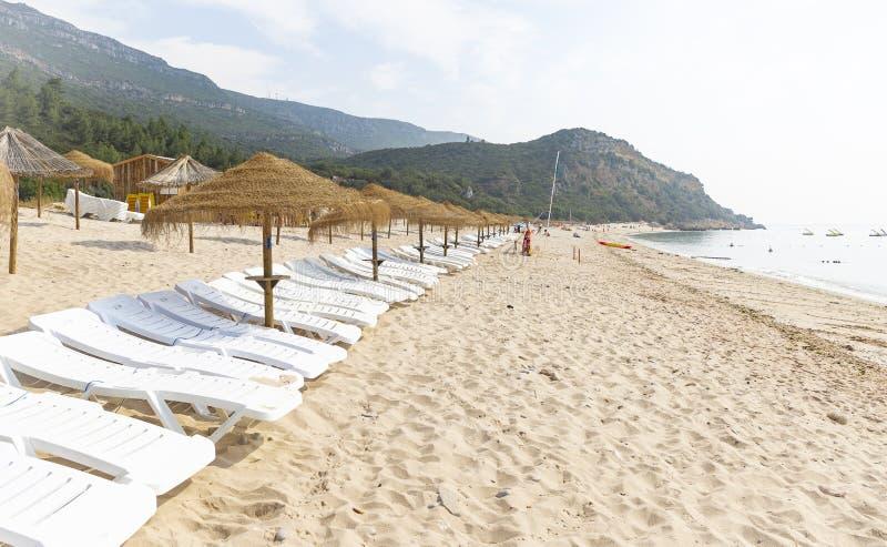 Straw Beach Umbrellas och soldagdrivare på den Portinho da Arrabida stranden arkivfoto