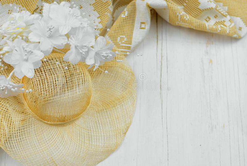 A straw bonnet with white and ivory silk flowers on a rustic wooden white washed background. Good for wedding or anniversary royalty free stock photo