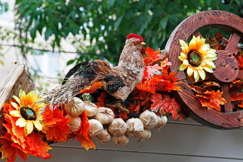 Straw cock, sunflowers, onions and wheel as autumn decoration for street festival `Moscow autumn` royalty free stock images