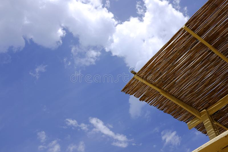 Straw cover the roof of a seaside terrace or veranda. Beautiful sky and clouds background. stock photos