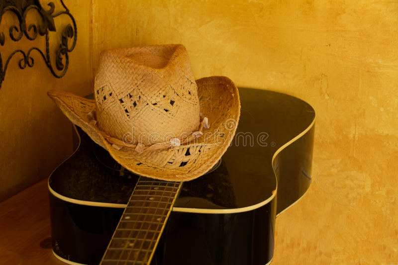 Straw Cowboy Hat på den svarta gitarren arkivfoto