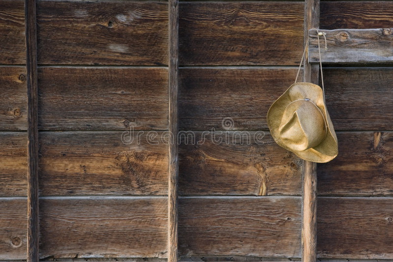 Straw cowboy hat and weathered wood royalty free stock photography