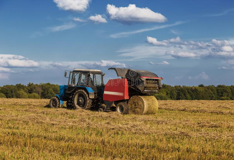 Straw harvesting with the help of a rotary roll forming machine in the unit with a tractor royalty free stock photography