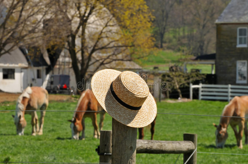 Straw hat with Amish farm in the background royalty free stock images