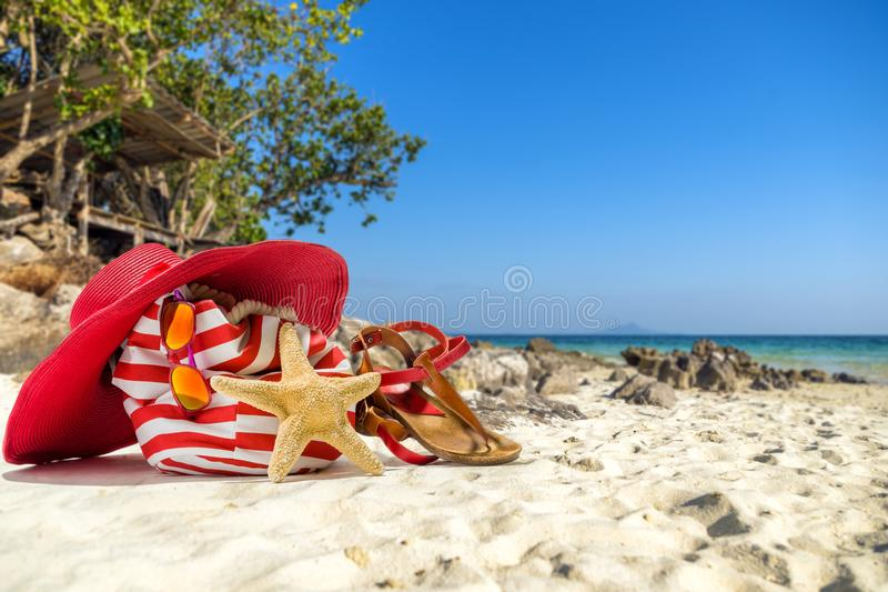 Straw hat, bag, sun glasses and flip flops on a tropical beach stock image