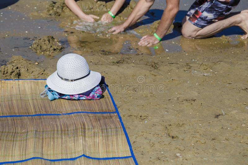 Straw hat, bag, sun glasses and flip flops on a tropical beach. royalty free stock images