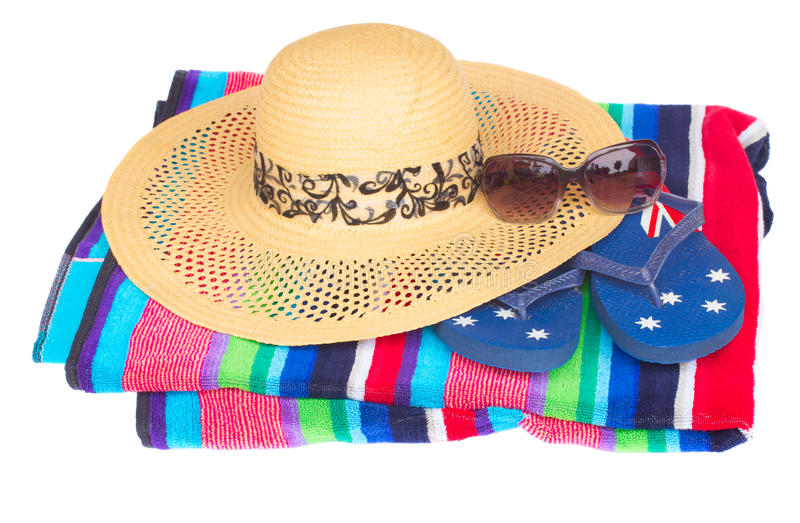 Straw hat on beach towel royalty free stock photos