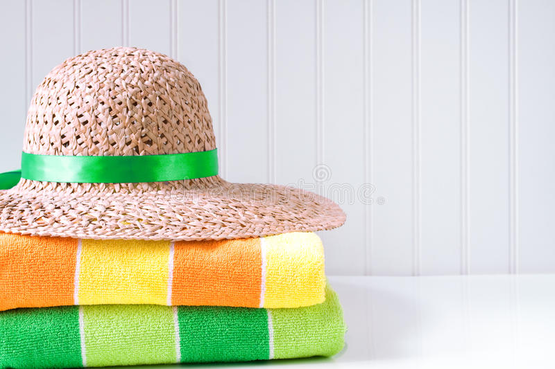 Straw hat with beach towels stock photography