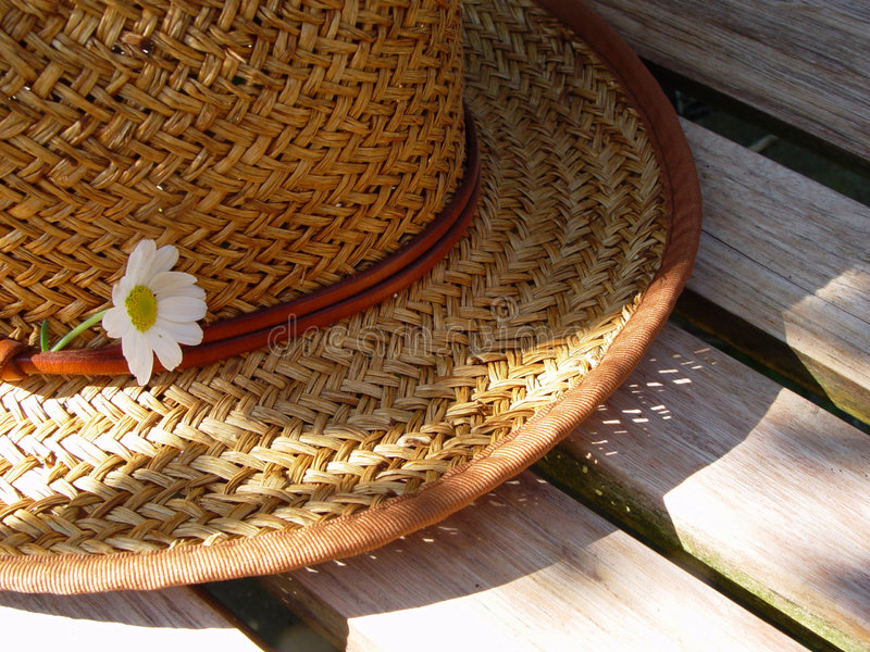 straw hat on a bench royalty free stock image