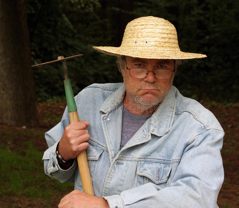 Straw hat and bibs. Potrait of a man in bib overalls and a straw hat holding a hoe royalty free stock image