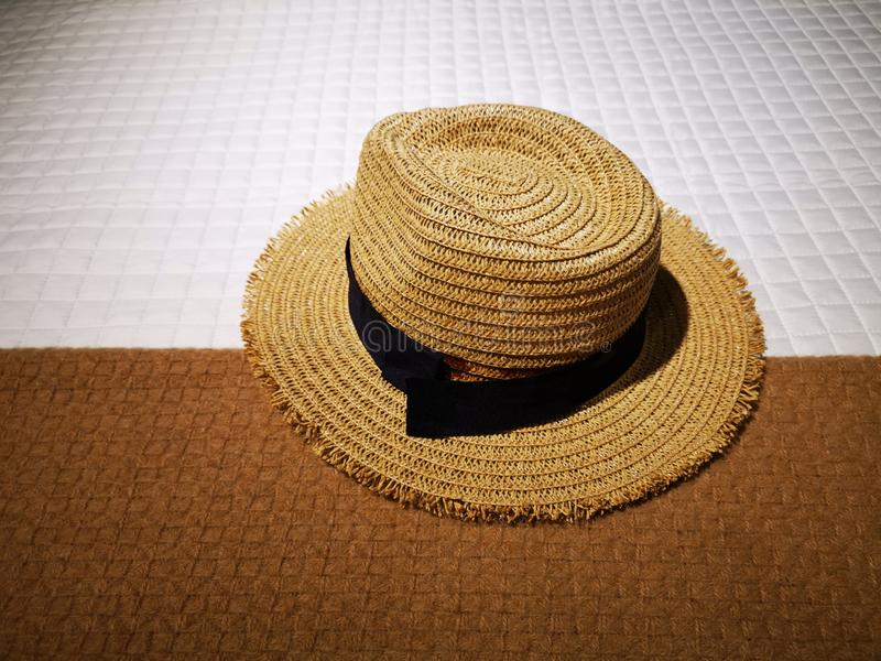 Straw hat with black ribbon on bed cover. Of two textured brown and white materials stock photos