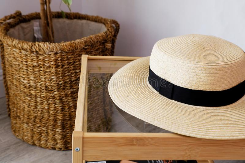 A straw hat with a black ribbon is on the coffee table in the living room. Plants in the background. Close up royalty free stock images