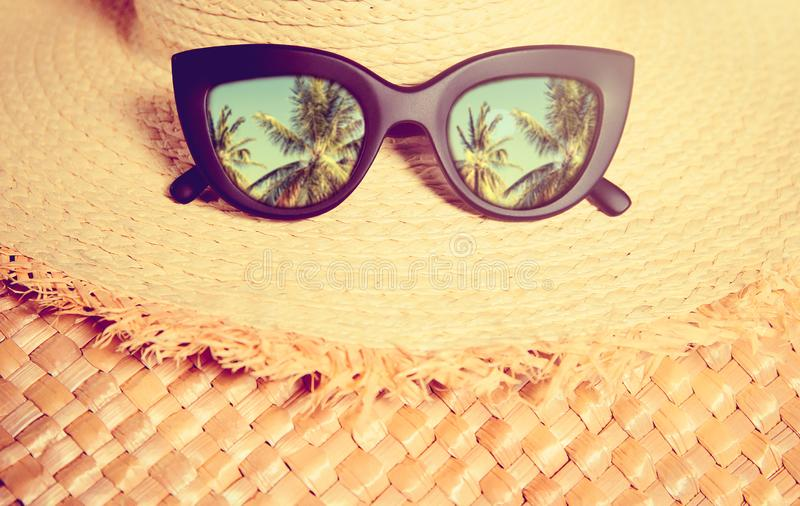 Straw hat with black trendy sunglasses with reflection of palms in them on a straw bag. royalty free stock photo
