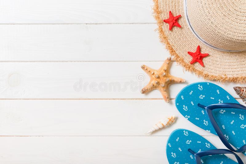 Straw hat, blue flip flops and starfish On a white wooden background. top view summer holiday concept with copy space royalty free stock photo