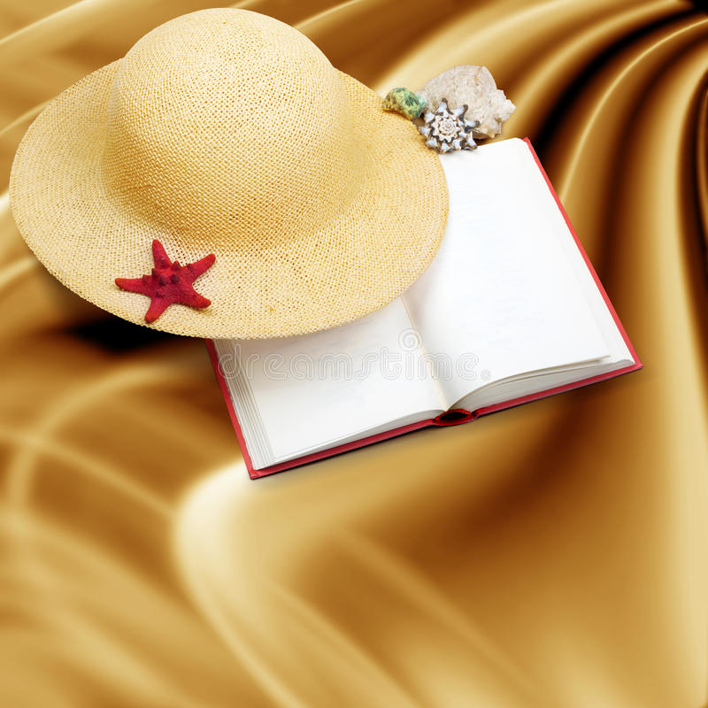 Straw hat with book and red starfish on shabby paper. Background royalty free stock photography