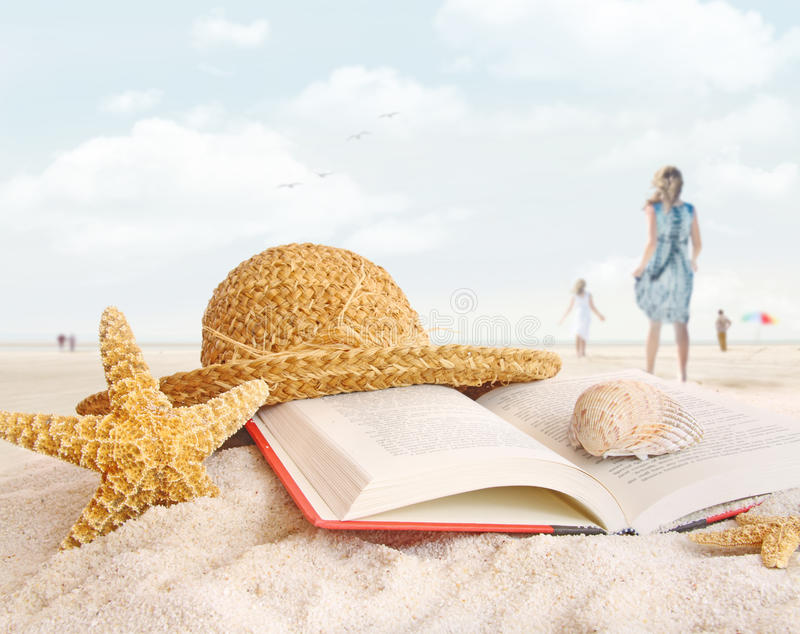 Straw hat , book and seashells in the sand stock photo
