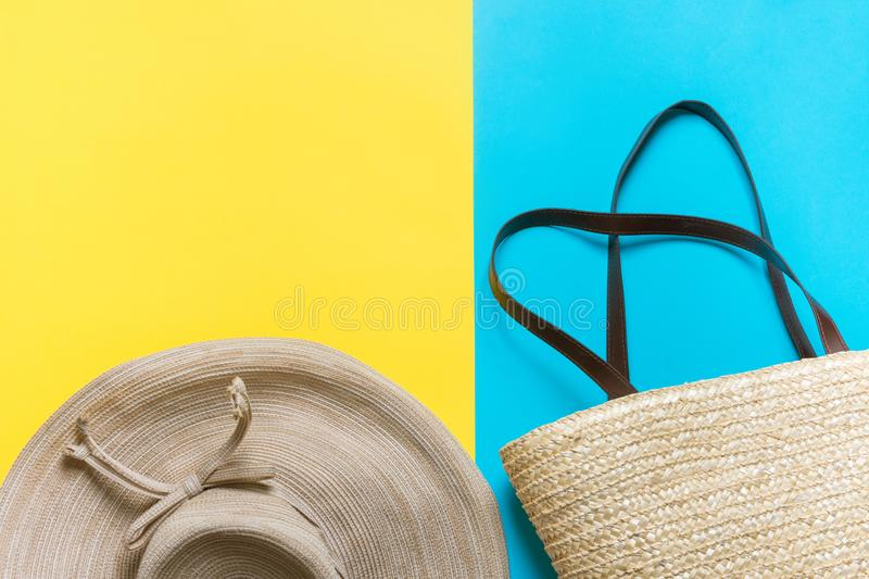 Straw hat with bow wicker handwoven beach bag on bright yellow mint blue duotone background. Travel vacation fashion. Concept. Poster banner with copy space stock photography