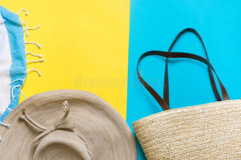 Straw hat with bow wicker handwoven beach bag striped fringed towel on bright yellow mint blue duotone background. Travel vacation fashion concept. Poster stock photography