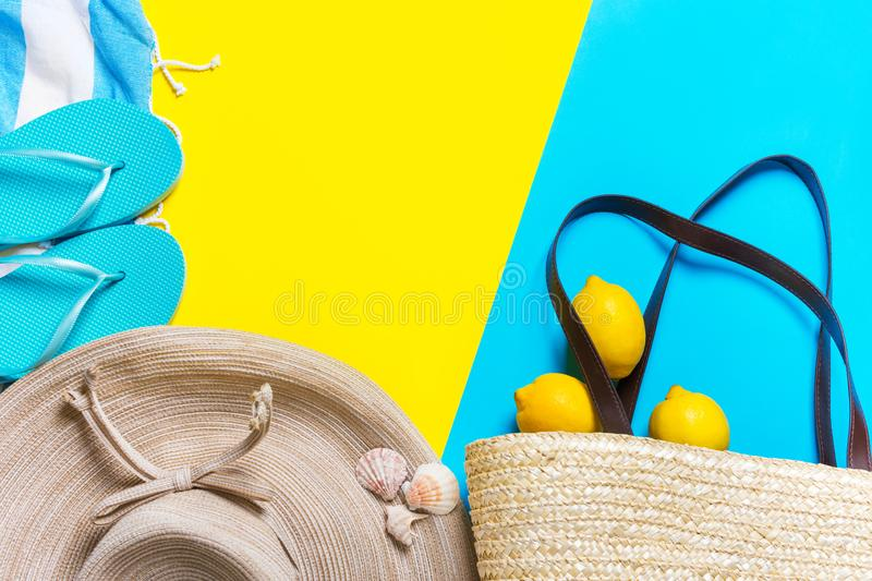 Straw hat with bow wicker handwoven beach bag striped fringed towel slippers citrus on bright yellow mint blue duotone background. Travel vacation fashion stock images
