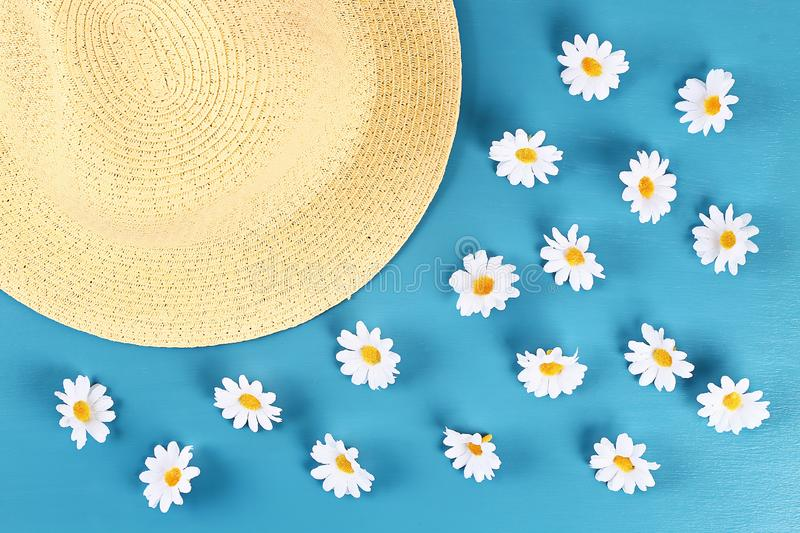 Straw hat with camomile on a blue background. Top view. Summer background. Flat lay stock photos