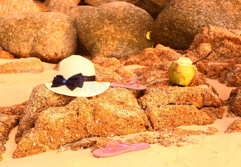 Straw hat coconut flip flops on the stony beach. Woman straw hat coconut and flip flops still life on the stony rock beach background stock photo