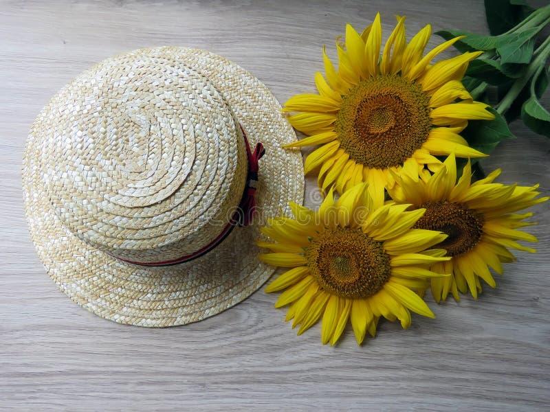 Straw Hat e girassóis no fundo de madeira fotos de stock royalty free